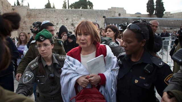 "Israeli policewomen detain a member of the religious group ""Women of the Wall"""