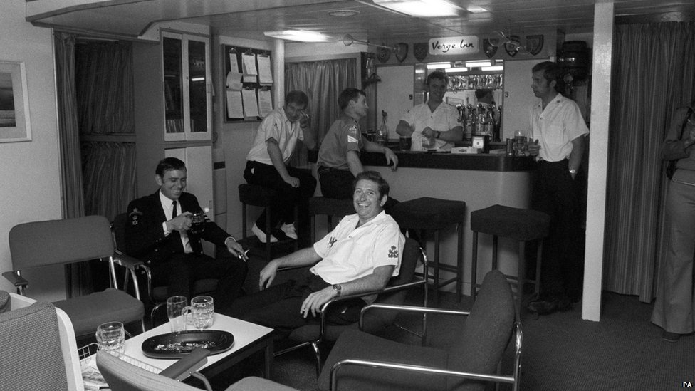 A view of the petty officers' mess in Britannia, with members relaxing over a drink, shows the modern furnishings after the vessel's major refit
