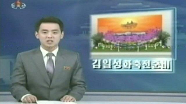 A North Korean newsreader delivering the news on TV