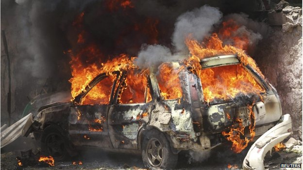 A car goes up in flames near the scene of a blast