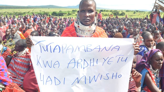 "A Maasai woman holds a sign that reads in Swahili: ""We will fight for our land until the end"""