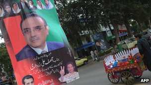 An ice cream vendor passes by an election banner for Mr Zardari in March 2013