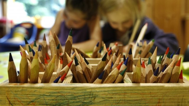 Colour pencils are pictured as children draw at a nursery school