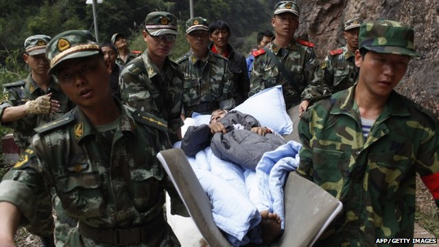 rescuers carrying an injured survivor to an emergency relief centre
