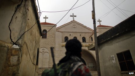 A rebel fighter looks at a church in Halassamiya (24 November 2012)