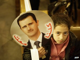 "A Syrian girl carries a picture of Bashar al-Assad saying ""we are with you"" during a Mass at a Greek Orthodox church in Damascus (9 January 2012)"