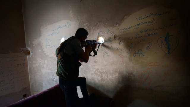 A Syrian rebel observes the movement of regime forces