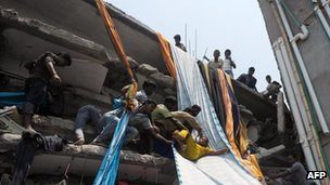 Bangladeshi garment workers assist a survivor onto a length of textile to be used as an evacuation slide