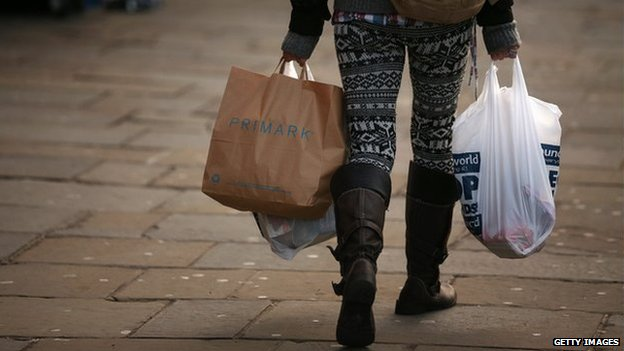 A woman carries several shopping bags from discount shops along Lewisham high street in December 2012