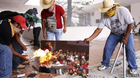 A group of teachers burn a picture of Mexico President Enrique Pena Nieto as they attack the offices of the ruling PRI to protest against an education overhaul in Chilpancingo, Guerrero state, Mexico, on Wednesday