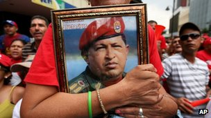 A supporter of Venezuela's President Nicolas Maduro holds a picture of late President Hugo Chavez during Mr Maduro's inauguration in Caracas, Venezuela, on 19 April 2013