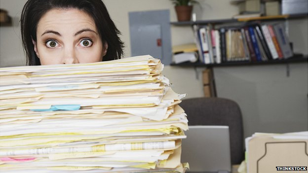 Woman looking over the top of files