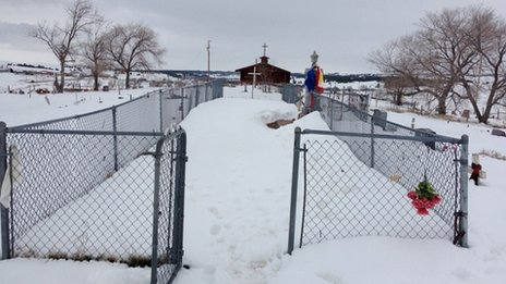 A snowy, fenced in area in front of a church