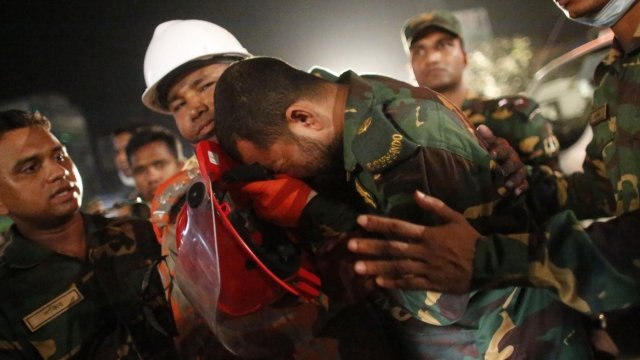 Rescuer workers help a colleague injured in the fire