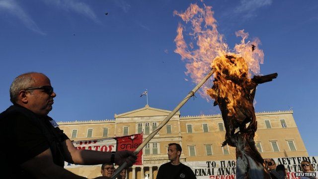 Protesters burn an effigy depicting a Greek worker during a rally against the government's austerity reform program in Athens