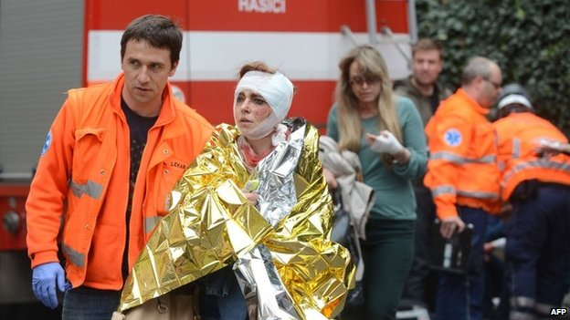 Rescue workers help a woman injured in the blast
