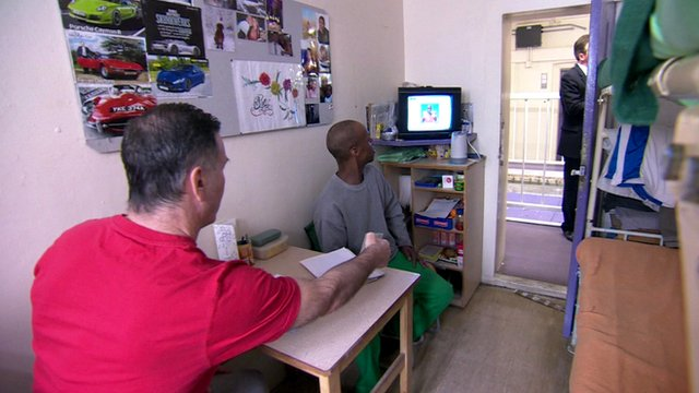 Two prisoners watching television in a cell