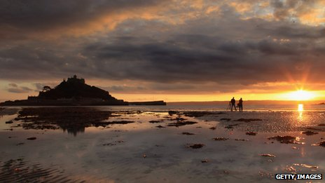 Visitors in silhouette as the sun sets over St Michael's Mount