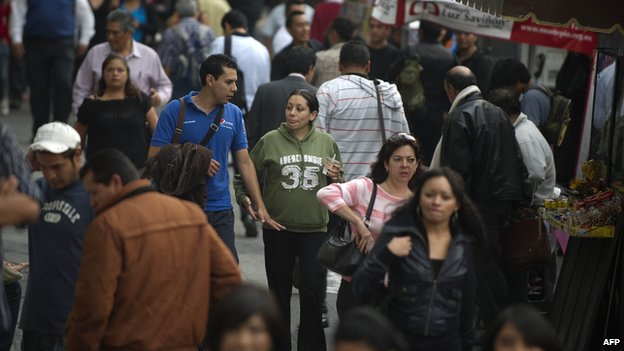 People walk on a crowded street in Mexico city