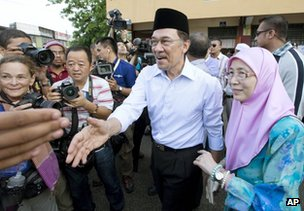 Anwar Ibrahim, centre, greets supporters with his wife Wan Azizah after voting at Penanti in Penang state in northern Malaysia, 5 May