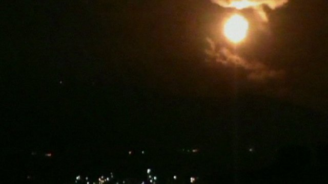 A still from unverified amateur footage shows the night sky lit up, apparently in Damascus
