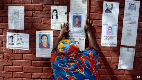 A woman grieves as she sticks a poster of a portrait of her family member on the wall of a school turned make-shift morgue on Tuesday 30, April, 2013