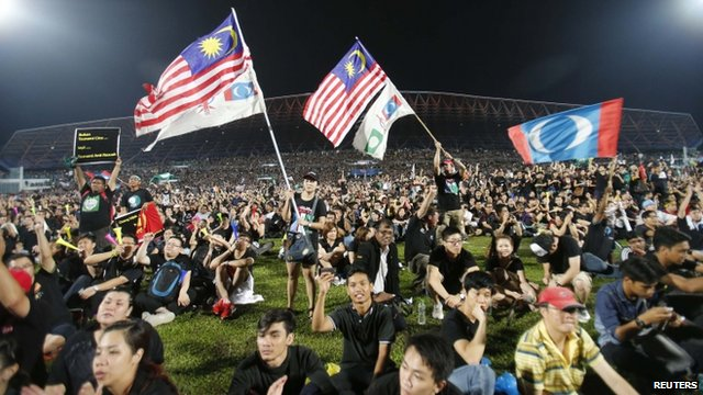Demonstrators wave flags as they attend a rally in protest of the Sunday's election result