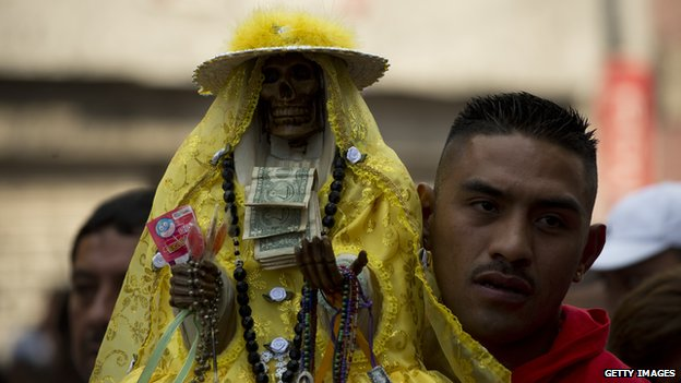 A man carries a statue of Santa Muerte during a procession in Mexico Cit on 1 November 2012