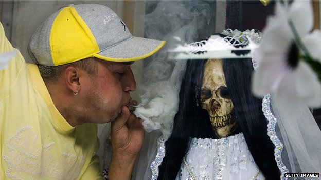 A devotee blows smoke at a statue of Santa Muerte on 1 November 2007