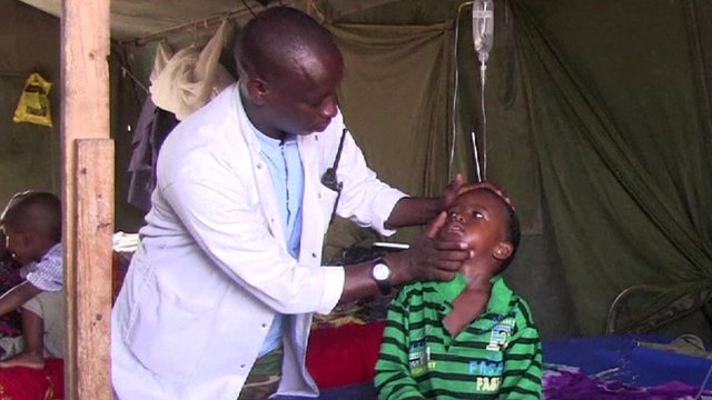 A doctor examines a child patient in a tent