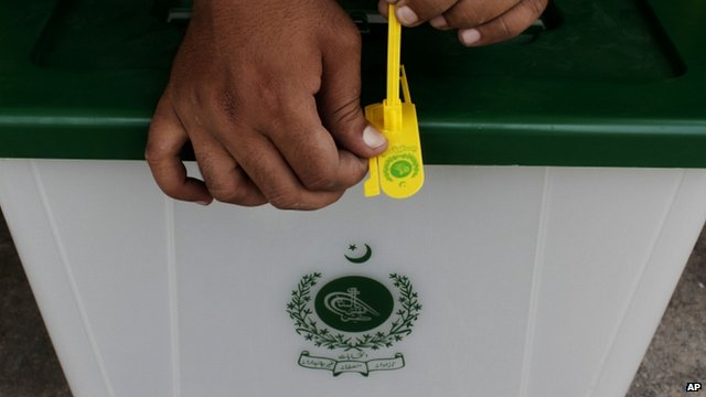 A Pakistan Election Commission worker seals a ballot box before dispatching them to polling stations in Karachi
