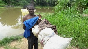 Jeti Matikmo, fisherman carrying a pole on his shoulder with bundles of fish