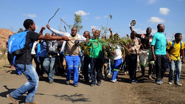 Striking Lonmin mine workers dance and sing while starting to gather next to a hill called Wonderkop