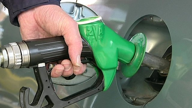 A hand holding a petrol pump to fill up a car