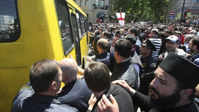 Anti-gay protesters try to attack a bus with gay activists who are being taken to safety by police from a rally in Tbilisi, Georgia
