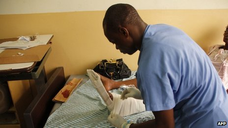 A nurse bandages Gerturde Sumbamala's left leg in a hospital in Accra, after it was broken in a crush in an evangelist church on 19 May 2013