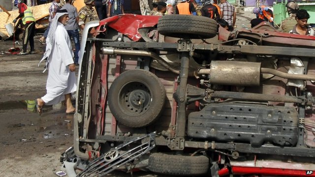 An overturned vehicle at the site of a car bomb attack in front of a popular restaurant in Basra