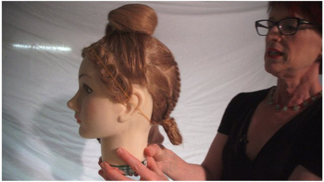 Janet Stephens looks at a hairstyle on a mannequin