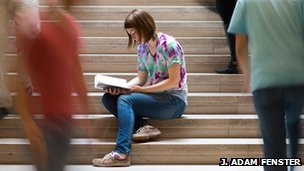 A woman focusing on reading a book while people rush around her