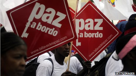 "Colombians hold placards reading ""Peace on board"" at a peace march on 9 April 2013"