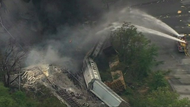 Firefighters pouring water on derailed carriages
