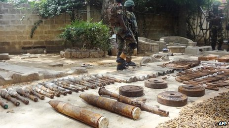 Soldiers stand around a cache of weapons display on 30 May 2013 in the Bompai area of the northern Nigerian city of Kano