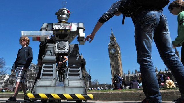 "People look at a mock ""killer robot"" in central London - part of a protest calling for a ban on such weapons in London on 23 April 2013"