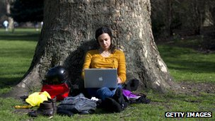 woman sitting under a tree on her laptop