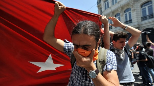 Protesters hold a large Turkish flag in front of a water cannon truck, Istanbul, 31 May 2013