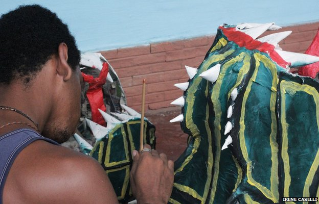 A dancer puts the finishing touches to his mask on 30 May 2013