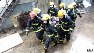 Chinese firefighters evacuate an injured worker from the Baoyuan poultry plant that caught fire in Dehui, north-east China's Jilin province on Monday