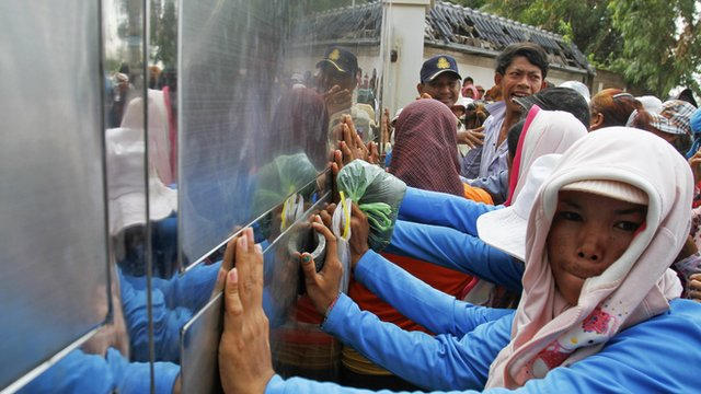 Garment workers push against the gates of a factory