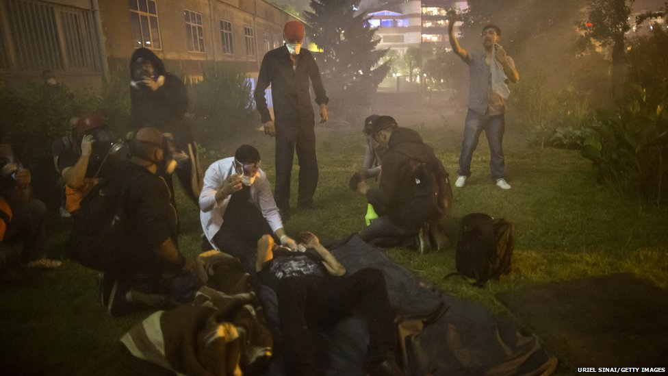 A medical team treats a protester as they are surrounded by a cloud of tear gas during clashes with Turkish police