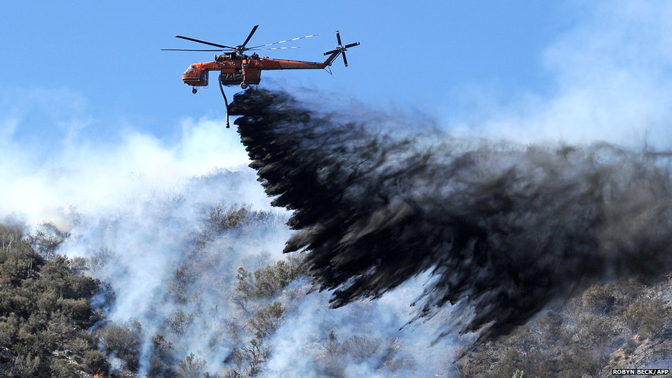 A firefighting helicopter drops fire retardant on a flare up at the Powerhouse Fire, near Lake Hughes, California